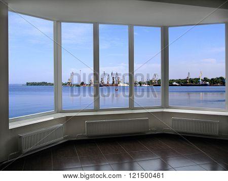 window overlooking the sea port docks and cranes in Berdyansk