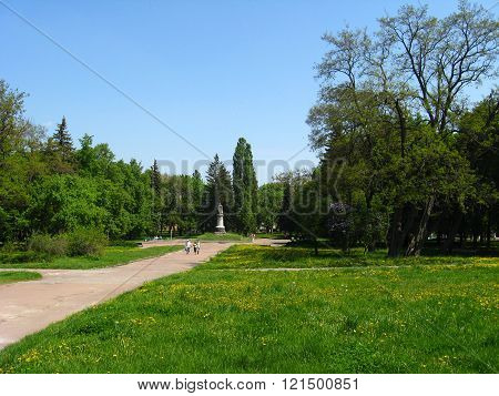 Chernihiv / Ukraine. 18 June 2015 : people walk in the city park with big trees and monument of Bohdan Khmelnytskyi.  18 June 2015 in Chernihiv / Ukraine.