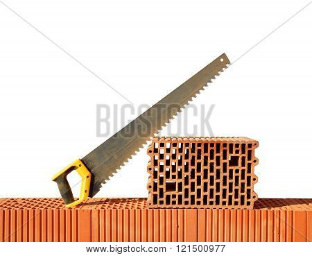 Brick wall with handsaw on bricks. Bricklaying work.