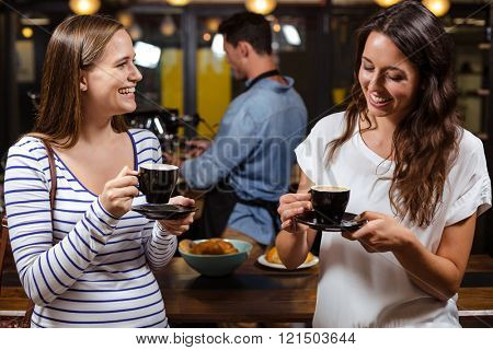 Smiling friends having coffee at the bar