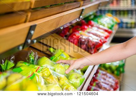 Womans hand holding plastic bag with apples in grocery shop
