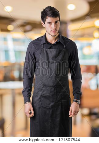 Young chef or waiter wearing black apron in restaurant