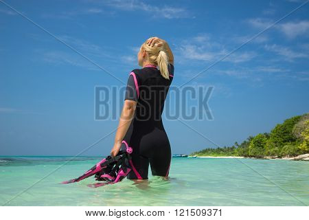 Woman Holding Mask And Flippers For Swimming On Tropical Beach