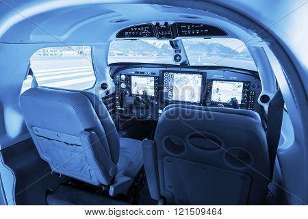 Detail view on flight simulator cockpit for small private airplanes blue colored.