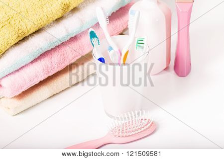 Toothbrushes towels and hairbrush in pastel tones. Group of white-pink objects on subject of hygiene. Close up small depth of sharpness