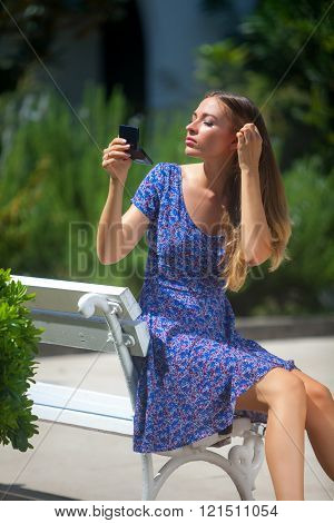 Young pretty woman sitting and prinking on a bench