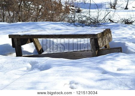 Old bench in the snow by a pond