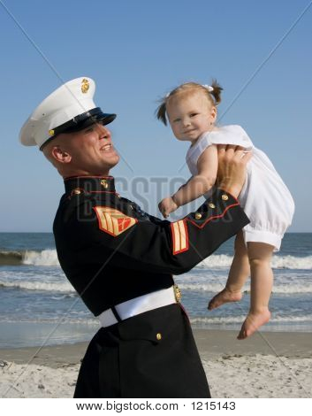 Marine And Daughter Playing At The Beach