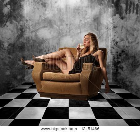 Portrait eines schönen Mädchens informell sitzend auf einem Stuhl und einem Glas Sekt