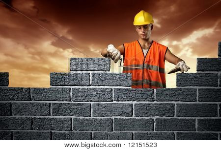 Mason in a hardhat building brick wall