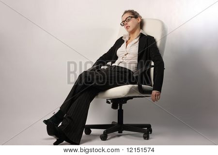 a tired beautiful businesswoman relaxing on a manager chair