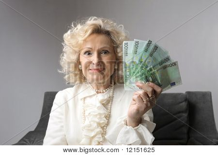 a smiling senior woman with money in her hand