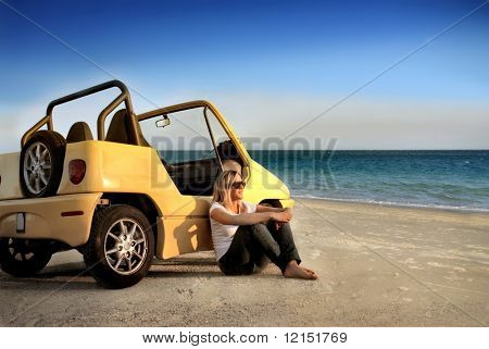young girl sitting on a beach with her car