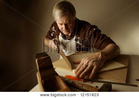 a joiner sawing a plank with an handsaw