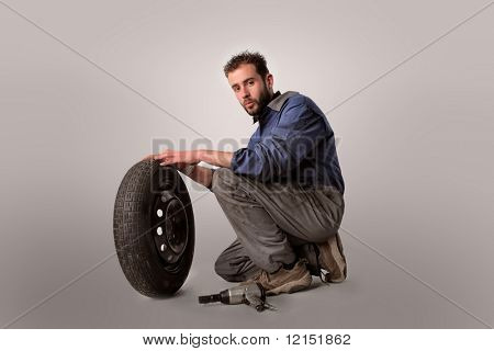 Portrait of an  auto mechanic with wheel and gun isolated on a white background