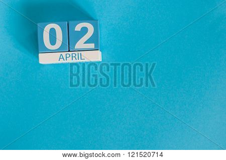 April 2nd. Image of april 2 wooden color calendar on blue background.  Spring day, empty space for t
