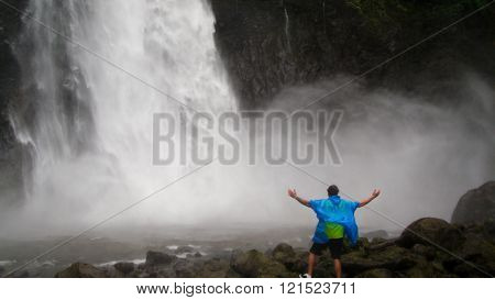 Man with wide spread arms challenging the powerful waterfall