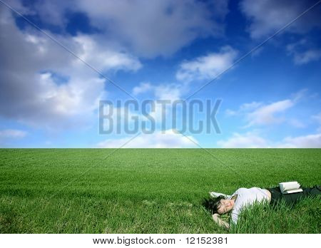 beautiful girl relaxing with a book in a grass field