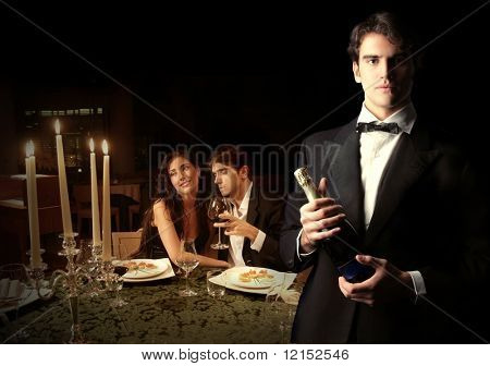 Waiter with bottle of wine and a couple on the background