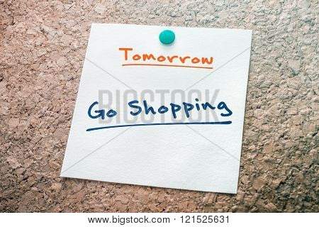Go Shopping Reminder For Tomorrow On Paper Pinned On Cork Board