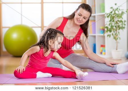 Mother and daughter doing fitness exercises on mat at home