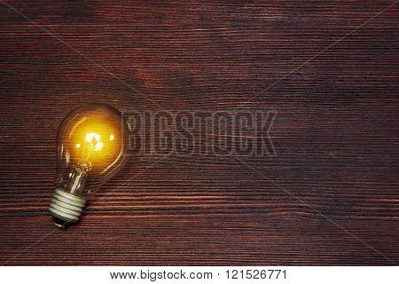 Lightning glass bulb on dark wooden backgound