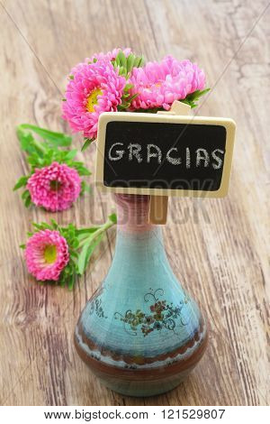 Gracias (which means thank you in Spanish) written on mini blackboard and pink daisies in porcelain