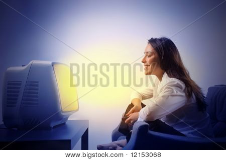 Girl sitting on the sofa and watching tv