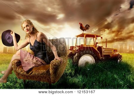 beautiful girl sitting on armchair in a grass field with a tractor