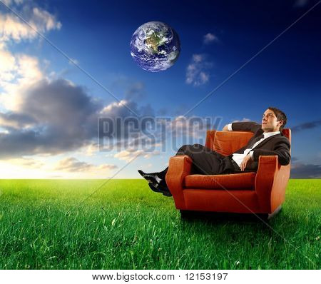 businessman sitting on an armchair in a grass field with planet earth in the sky
