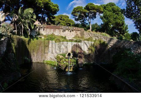 Fountain in a park with water flowing from an old amphora, Cagliari, Sardinia