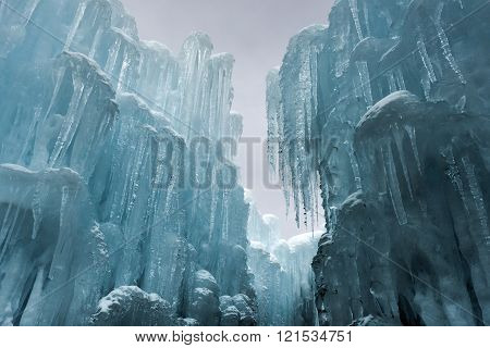 Translucent blue icicles in a frozen ice wall.