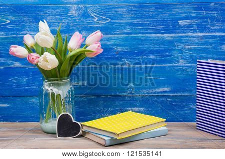 Colorful tulips flowers and yellow book on blue wooden desk table background. Copy space