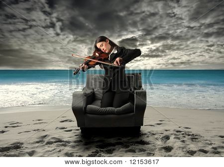 business woman playing violin alone on the beach