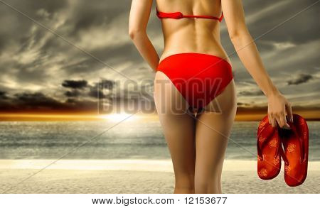 bottom of woman in bikini on the beach