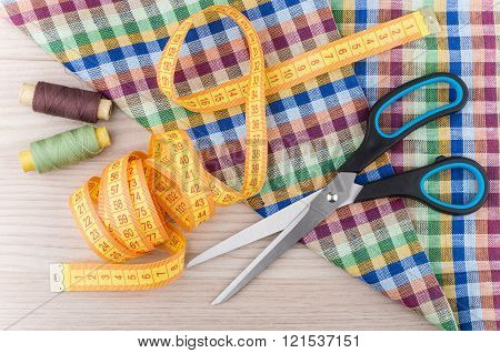Scissors, Tape-line, Threads And Fabric On Wooden Table