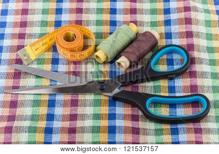 Sartorial scissors, tape-line, threads and needles on fabric