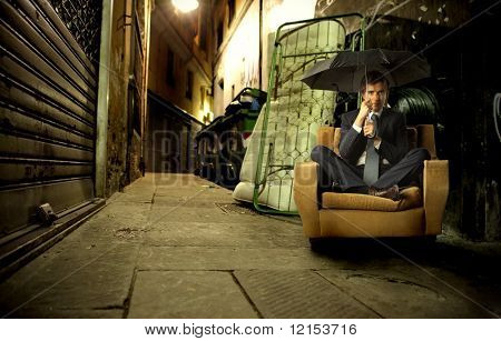 businessman with umbrella sitting on armchair in a city street