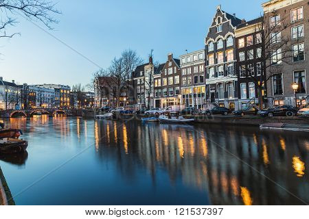 AMSTERDAM NETHERLANDS - 16TH FEBRUARY 2016: A view along the Amsterdam Canals at twilight. Buildings people bridges cars and boats can be seen.