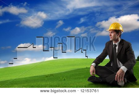 businessman with hard hat planning to build a city