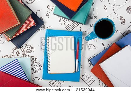 Office table desk with blue supplies, white blank note pad, cup, pen, pc, crumpled paper, flower on