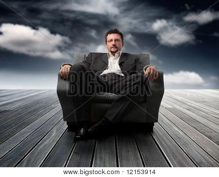 sentado en el sillón contra un cielo de hombre de negocios