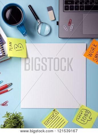 Office table desk with supplies, blank note pad, cup, pen, pc, crumpled paper, flower on blue backgr
