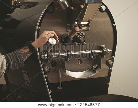 Tattooed Hand Pulls Lever In Coffee Roasting Machine