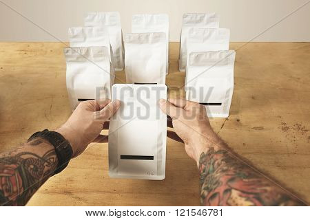 Two brutal tattooed roaster hands hold sealed package bag with tea or coffee ready for delivery and