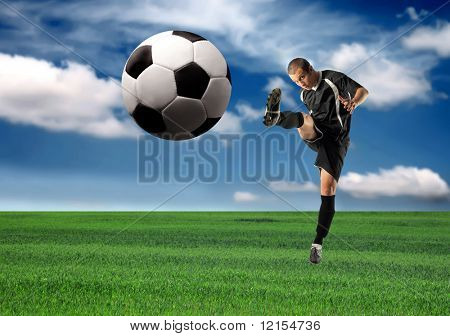 soccer or football player kicking a ball in a grass field