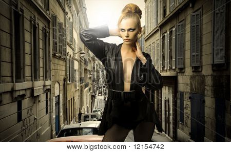 beautiful female model in elegant clothes against a cityscape