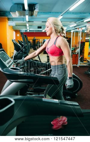 Athletic girl adjusting the treadmil in gym