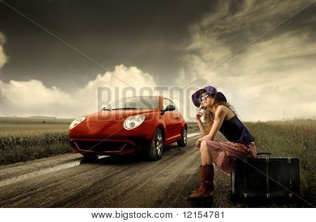 girl hitchhiking on a suitcase and a car running on the road
