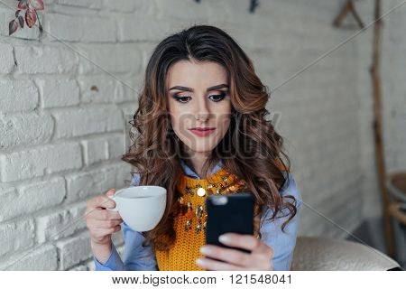 Beautiful girl drinking tea and working with phone